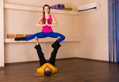 Acrobatic yoga in a studio. Man and a women performing acrobatic yoga in a studio Royalty Free Stock Photos