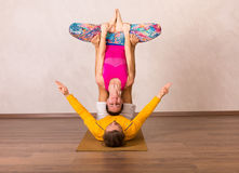 Acrobatic yoga in a studio. Man and a women performing acrobatic yoga in a studio stock photos