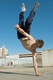 Acrobatic young break dancer. Closeup of acrobatic teenage break dancer balancing on one hand outdoors Royalty Free Stock Image