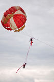Acrobatics in air. Two girls are performing acrobatics in mid air by hanging under a huge Parachute over Lake Qionghai,Xichang,Sichuan,China Royalty Free Stock Images