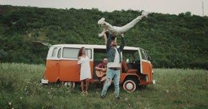 Acrobatisch element bij de picknick, dansend paar, sommigen die van vriend het spelen bij de gitaar, in de retro bestelwagen zitt stock video