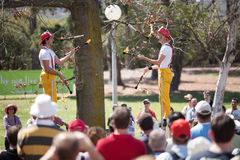 Acrobats and flame jugglers busking Stock Images