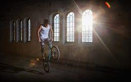 Acrobazia di BMX e guida di salto in un corridoio con luce solare Immagini Stock