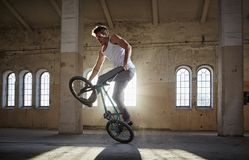 Acrobazia di BMX e guida di salto in un corridoio con luce solare Immagini Stock Libere da Diritti