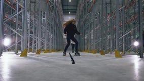 Acrobazie di pattinaggio a rotelle nel centro di logistica Trucchi di slalom stock footage