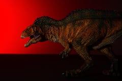 Acrocanthosaurus met vleklicht op het hoofd en rood licht op achtergrond royalty-vrije stock afbeelding