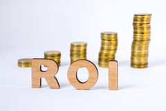 Acronym ROI of three-dimensional letters is in foreground with growth columns of coins on blurred background. ROI concept for fina stock photo