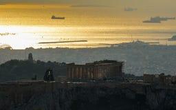 Acropoli con il panteon, le costruzioni bianche architettura, la montagna, gli alberi ed il tramonto dorato del mare a Atene immagine stock libera da diritti