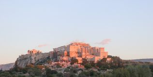 The Acropolis in Athens Greece at sunset with the pink light reflecting off it and pink clouds in the sky - people are watching th Stock Photos