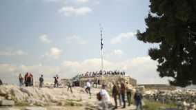 Acropolis Hill near Greek national flag people silhouettes tilt-shift,. Unrecognizable people on the Acropolis Hill near Greek national flag visiting the stock video footage