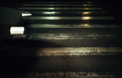 Across The Crosswalk. Night scene of a street crosswalk, one car in motion blur on left side, conceptual composition about traffic issues Stock Photography