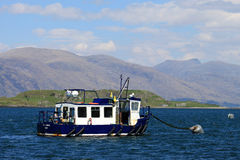 Across Loch Linnhe to Kingairloch from Port Appin. Small boat anchored in the top end (north east) of Lynn of Lorn off Port Appin, Argyll and Bute district Stock Photos
