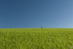 Across the meadow 2. A young boy strolls across an open meadow under a bright blue sky royalty free stock photo