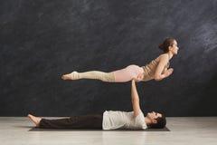 Acroyoga di pratica delle giovani coppie sulla stuoia insieme immagine stock