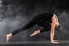 Acroyoga Junge Frau übendes acro Yoga auf Matte im Studio Hatha-Yoga Stockfotos