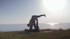 Acroyoga, two sporty people practicing yoga in pair on nature sunset background, young couple doing stretching exercise. On the mountain stock video footage