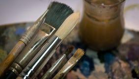 Acrylfarbe und Bürsten auf hölzerner Palette Stockfotografie