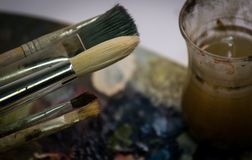 Acrylfarbe und Bürsten auf hölzerner Palette Lizenzfreie Stockbilder
