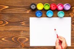 Acrylfarbe, weißes Blatt und Hand auf einem hölzernen Hintergrund Stockbild