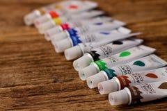 Acrylfarben in den Bombenrohren auf hölzernem Brett Lizenzfreie Stockbilder
