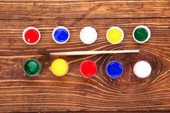Acrylfarben in den Gläsern nahe der Bürste, auf dem Retro- hölzernen backg Lizenzfreies Stockbild