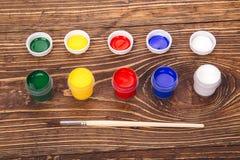Acrylfarben in den Gläsern nahe der Bürste, auf dem Retro- hölzernen backg Lizenzfreie Stockfotos