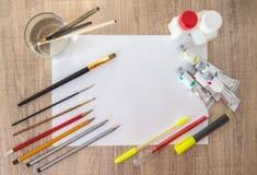 Acrylfarben, Malerpinsel, Bleistifte auf Weißbuch Leerer Raum in der Mitte Stockfoto