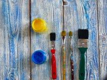 Acrylfarben und farbige Bürsten auf einem authentischen Hintergrund von handgemachtem mit copyspace Stockfotos