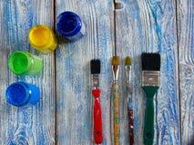 Acrylfarben und farbige Bürsten auf einem authentischen Hintergrund von handgemachtem mit copyspace Lizenzfreie Stockfotos