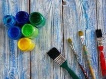 Acrylfarben und farbige Bürsten auf einem authentischen Hintergrund von handgemachtem mit copyspace Stockfotografie