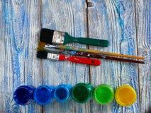 Acrylfarben und farbige Bürsten auf einem authentischen Hintergrund von handgemachtem mit copyspace Stockfoto