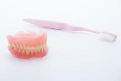 Acrylgebisse mit Zahnbürste auf weißem Hintergrund Stockfotografie