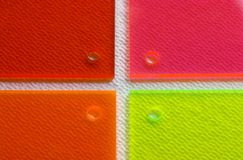 Acrylic 6. Close take of an multicoloured four acrylic pieces over textured paper Royalty Free Stock Photo