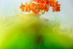 Acrylic background with mixing green, yellow and orange paint in water royalty free stock photography