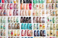 Acrylic fingernails on display. Artificial acrylic nails painted in various designs on display in nail salon stock images