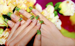 Acrylic nails. Acrylic nails with green pieces of acrylic and Golden sand royalty free stock images