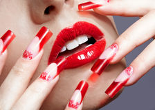 Acrylic nails manicure. Fingers with red french acrylic nails manicure and paiting royalty free stock photos