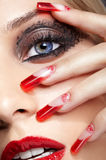 Acrylic nails manicure. Fingers with red french acrylic nails manicure and paiting stock photos