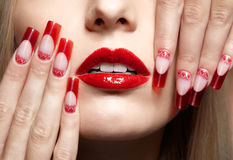 Acrylic nails manicure. Fingers with red french acrylic nails manicure and paiting stock photo