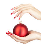Acrylic nails manicure. Hands with red french false acrylic nails manicure holding christmas ball isolated on white background stock image