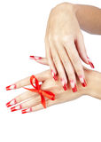 Acrylic nails manicure. Hands with red french acrylic nails manicure and painting with bow on finger isolated white background stock images