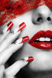 Acrylic nails manicure. Woman part of face with eyes closed by red ribbon and with red french acrylic nails manicure stock photo