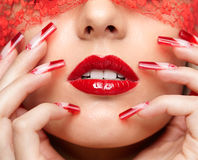 Acrylic nails manicure. Woman part of face with eyes closed by red ribbon and with red french acrylic nails manicure royalty free stock image