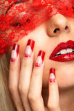Acrylic nails manicure. Woman part of face with eyes closed by red ribbon and with red french acrylic nails manicure royalty free stock photo