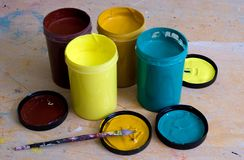 Acrylic Paint. A group of 4 acrylic paint tubs on a work bench royalty free stock image