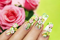 Acrylic roses. Art nail design with acrylic roses on the French manicure on a green background with roses stock images