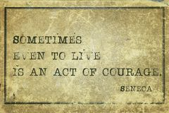 Act courage Seneca. Sometimes even to live is an act of courage - ancient Roman philosopher Seneca quote printed on grunge vintage cardboard royalty free stock image