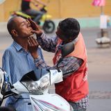 Act of Kindness. Armless man being shaved by motorcycle taxi driver Stock Image