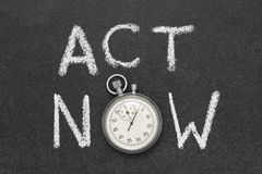 Act now. Phrase handwritten on chalkboard with vintage precise stopwatch used instead of O Royalty Free Stock Photo