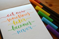 ACT NOW SOMETIMES LATER BECOMES NEVER hand-lettered in notebook. With brush pen and cup of coffee on wooden desk royalty free stock photos